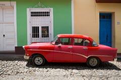 在五颜六色的房子前面的红色老汽车,古巴 免版税库存照片