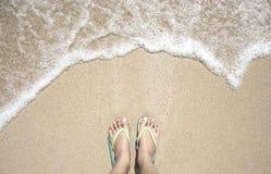 在五颜六色的拖鞋的妇女脚在与行动的海滩挥动 库存图片
