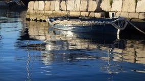 在五颜六色的日落的小船在力耶卡港口有都市产业和货物天才的在克罗地亚 库存照片