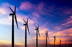 在五颜六色的日落的风轮机剪影 免版税库存照片