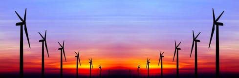 在五颜六色的日落的风轮机剪影 免版税图库摄影
