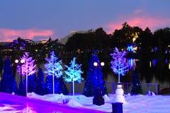 在五颜六色的日落背景的雪人和假日树在国际推进地区 库存照片
