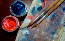 在五颜六色的旧布的两把刷子与两个树胶水彩画颜料罐头 库存照片
