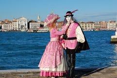 在五颜六色的服装的美好的夫妇和面具,在圣马可广场的看法 免版税库存图片