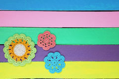 在五颜六色的木桌上的美妙的钩针编织小垫布 库存照片