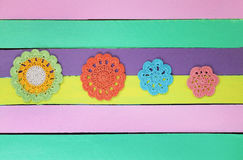 在五颜六色的木桌上的美妙的钩针编织小垫布 图库摄影