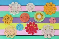 在五颜六色的木桌上的美妙的钩针编织小垫布 库存图片