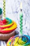 在五颜六色的杯形蛋糕的灼烧的蜡烛与奶油 库存图片