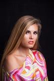 在五颜六色的柔滑的礼服的秀丽年轻白肤金发的妇女画象 库存图片