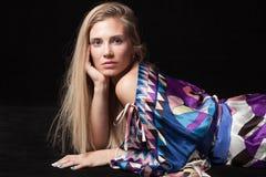 在五颜六色的柔滑的礼服的年轻美丽的白肤金发的妇女画象 免版税库存图片