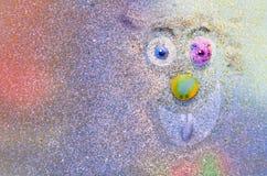 在五颜六色的沙子墙壁上的微笑的幸运的面孔 图库摄影