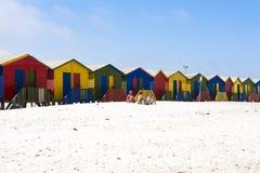 在五颜六色的海滩小屋前面的白色海滩 免版税库存照片