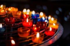在五颜六色的烛台的灼烧的蜡烛在教会里 免版税库存照片