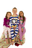 在五颜六色的睡衣的三个孩子坐毯子 免版税库存照片