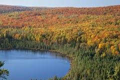 在五颜六色的秋天结构树之中的蓝色湖在明尼苏达 库存图片