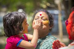 在五颜六色的粉末盖的人们在达卡,孟加拉国洗染庆祝Dol Utsav节日 免版税库存照片