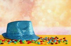 在五颜六色的糖果旁边的蓝色发光的党帽子 免版税库存照片