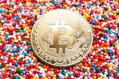 在五颜六色的糖果背景关闭的金黄Bitcoin硬币 库存图片