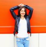 在五颜六色的红色的城市塑造美丽的微笑的少妇佩带的岩石黑夹克,牛仔裤 免版税库存照片
