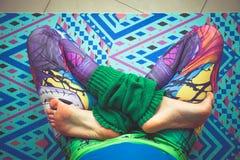 在五颜六色的绑腿的妇女腿在莲花摆在从看法上  免版税库存照片