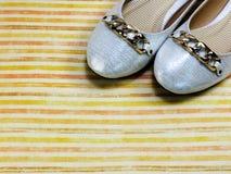 在五颜六色的背景的女性平的芭蕾舞鞋 图库摄影