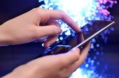 在五颜六色的背景的手感人的巧妙的电话 库存照片