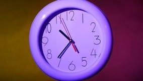 在五颜六色的背景的白色时钟 慢的行动 股票录像