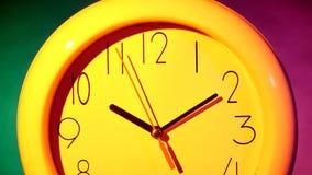 在五颜六色的背景的黄色时钟 股票视频