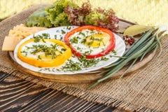 在五颜六色的胡椒的煎蛋在一个棕色老木板 库存图片