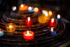 在五颜六色的蜡烛台的灼烧的蜡烛在教会里 库存照片