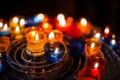 在五颜六色的蜡烛台的被点燃的蜡烛在教会里 免版税图库摄影