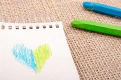在五颜六色的蜡笔旁边的笔记本 免版税图库摄影
