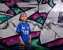 在五颜六色的街道画前面的时髦年轻男孩 图库摄影