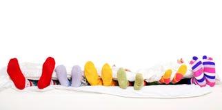 在五颜六色的袜子的愉快的家庭在白色床上 免版税图库摄影