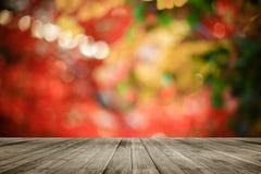 在五颜六色的被弄脏的背景前面的木板空的桌 在bokeh光的透视棕色木头 库存照片