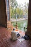 在五颜六色的西班牙正方形的创造性的沉思艺术家绘画在塞维利亚,西班牙 库存图片