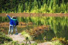 在五颜六色的运动衫的年轻夫妇在火山的湖前面站立 库存图片