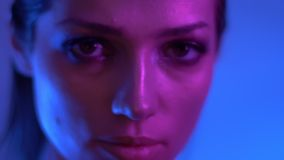 在五颜六色的霓虹灯轮的未来派时装模特儿对固定照相机和手表严肃和入它在演播室 股票视频