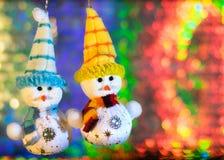 在五颜六色的bokeh背景的两个玩具雪人  免版税图库摄影