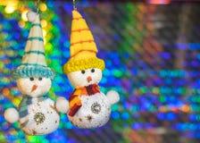 在五颜六色的bokeh背景的两个玩具雪人  免版税库存图片