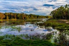 在五颜六色的Creekfield湖的反射有有趣的云彩形成和秋天颜色的。 免版税库存照片