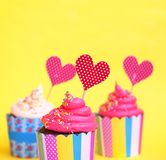 在五颜六色纸烘烤的三块鲜美草莓杯形蛋糕托起,与生日快乐贺卡,在黄色背景 党后面 免版税库存照片