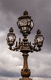 在亚历山大III桥梁的街道灯笼反对多云天空 库存图片