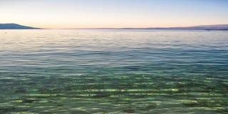 在亚得里亚海海岛Pag,在日落以后的克罗地亚海岸的透明的水  免版税库存图片