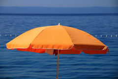 在亚得里亚海附近的橙色沙滩伞在Brela,克罗地亚 免版税库存图片