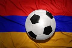 在亚美尼亚的国旗的黑白橄榄球球 免版税库存图片