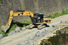 在亚诺河河岸附近的黄色挖掘机机器工作,在佛罗伦萨 库存照片