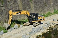 在亚诺河河岸附近的黄色挖掘机机器工作,在佛罗伦萨 免版税库存图片
