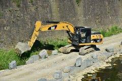 在亚诺河河岸附近的黄色挖掘机机器工作,在佛罗伦萨 免版税库存照片