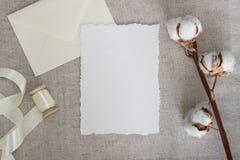 在亚麻布的被撕毁的边缘纸牌与棉花花和丝绸丝带 婚礼文具大模型 书法模板 免版税库存照片